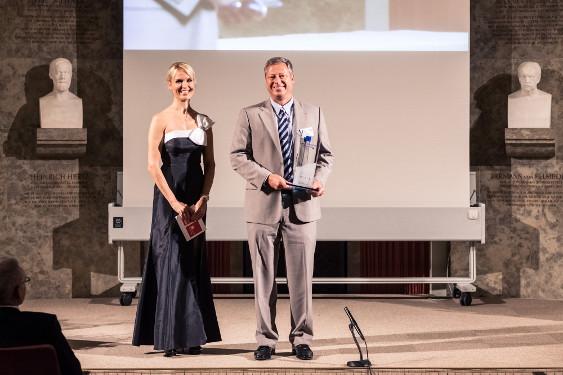 Gerd Czekalla, Business Unit Director Immunologie und Infektologie, Janssen-Cilag und Tamara Sedmak, Moderatorin, auf der Preisverleihung