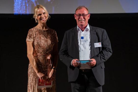 Walter Aigner, Regionaler Verkaufsleiter, Bayer Vital und Tamara Sedmak, Moderatorin, auf der Preisverleihung /© Eurecon Verlag / Denis Jung
